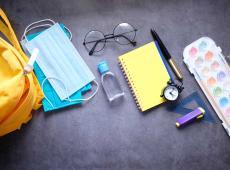 studentenschooltaspakket met ontsmettingsmiddel en een mondmasker