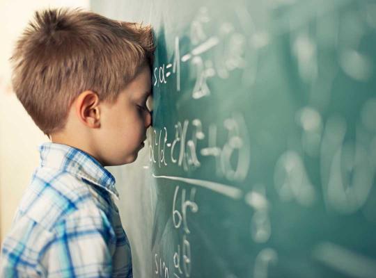 Kind leunt met hoofd op schoolbord